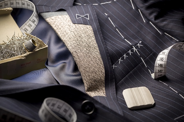 A suit being made with white stitches