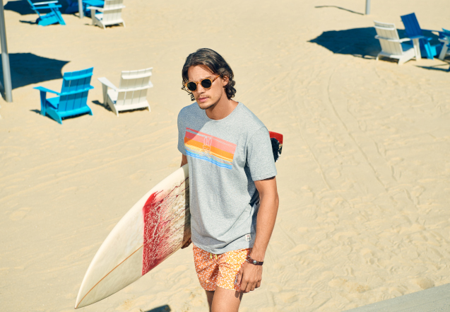 man with surf board in psycho bunny t shirt