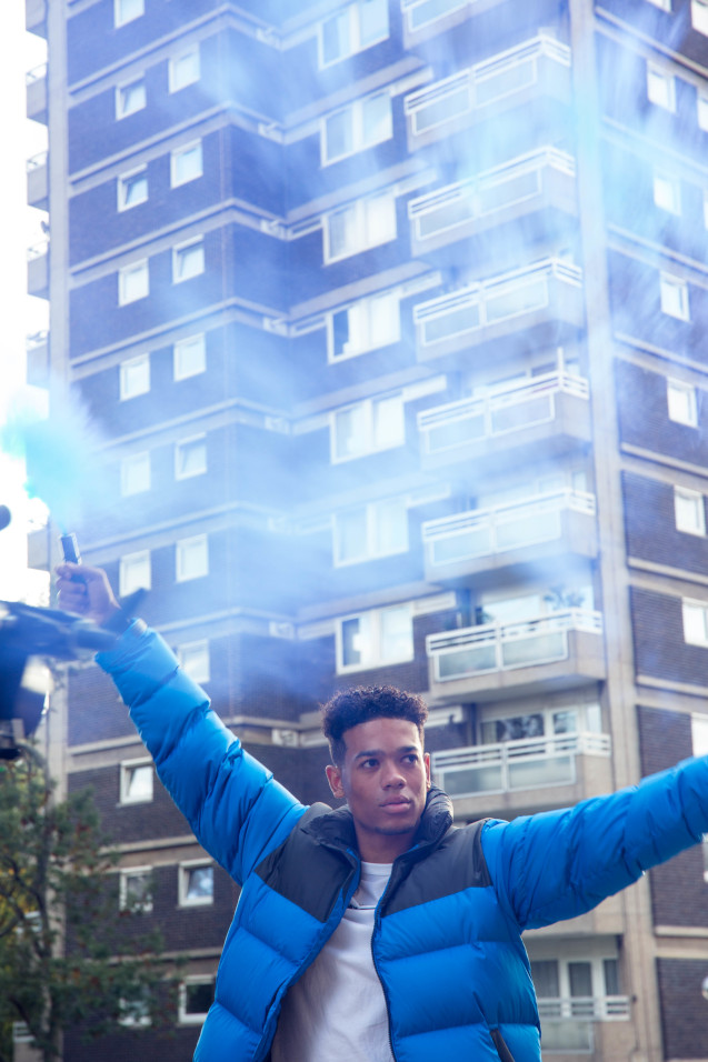 Man in blue Puffer Jackets Holding Smoke bombs
