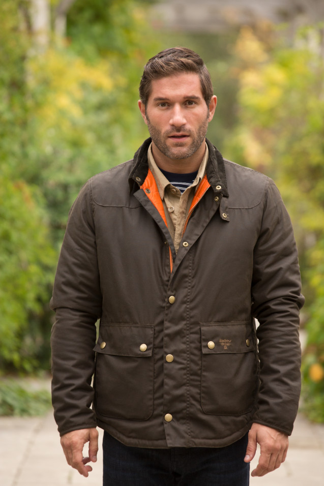 A man wears a thick brown parka coat in a park