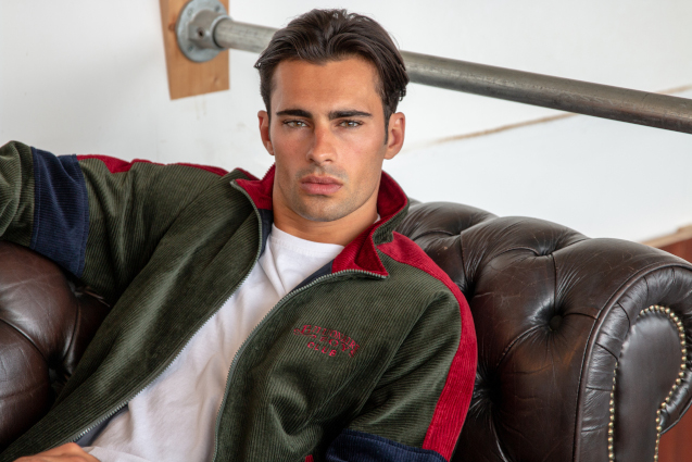 man sat on couch in green jacket