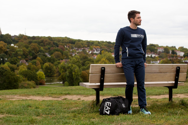 A Man leaning against a bench wearing a sporty Hugo Boss tracksuit