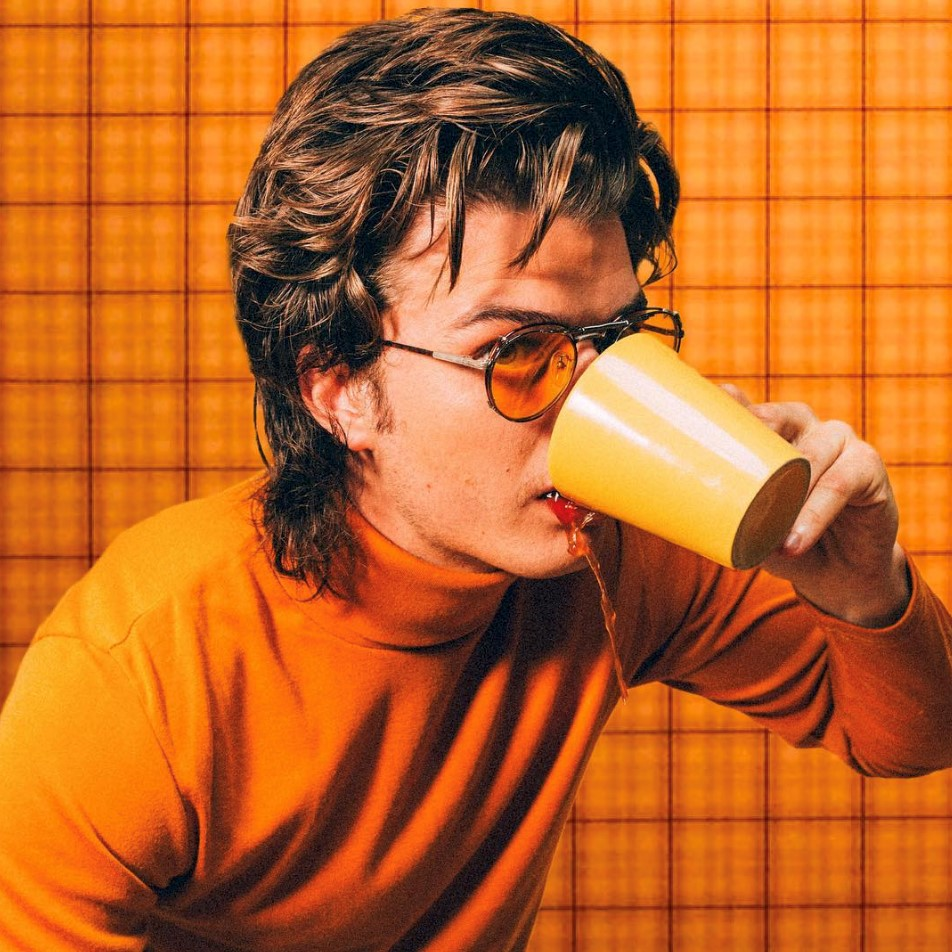 Joe Keery in orange sweater