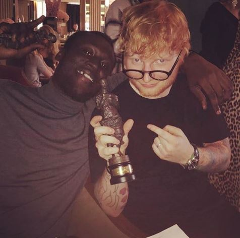 Stormzy in a grey turtleneck jumper next to ed sheeran