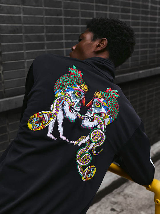 Man wearing a Adidas x Tanaami hoodie with art on the back.