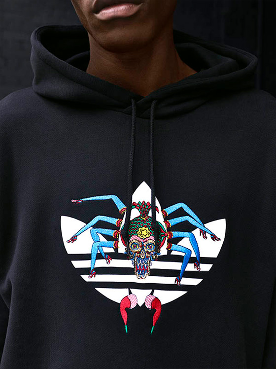 Close up of a Adidas x Tanaami hoodie with art on the logo.
