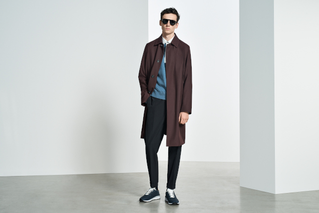 A man is stood staring at the camera behind a white wall. He is wearing a brown coat, blue jumper, sunglasses and black chinos that are slightly baggy. He has black trainers on his feet to match.