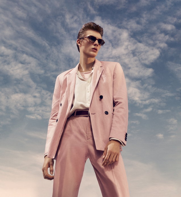A man is stood looking past the camera. He is wearing sunglasses, a pink blazer, white shirt and pink chinos, all from Hugo Boss. There is a blue sky behind him.