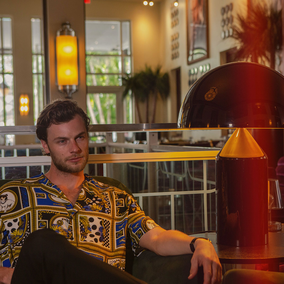 Man sat in bar wearing patterned shirt