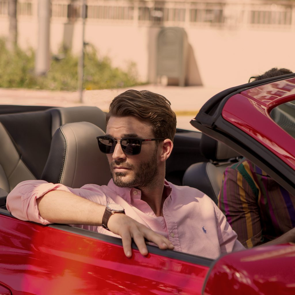 man in red car wearing sunglasses