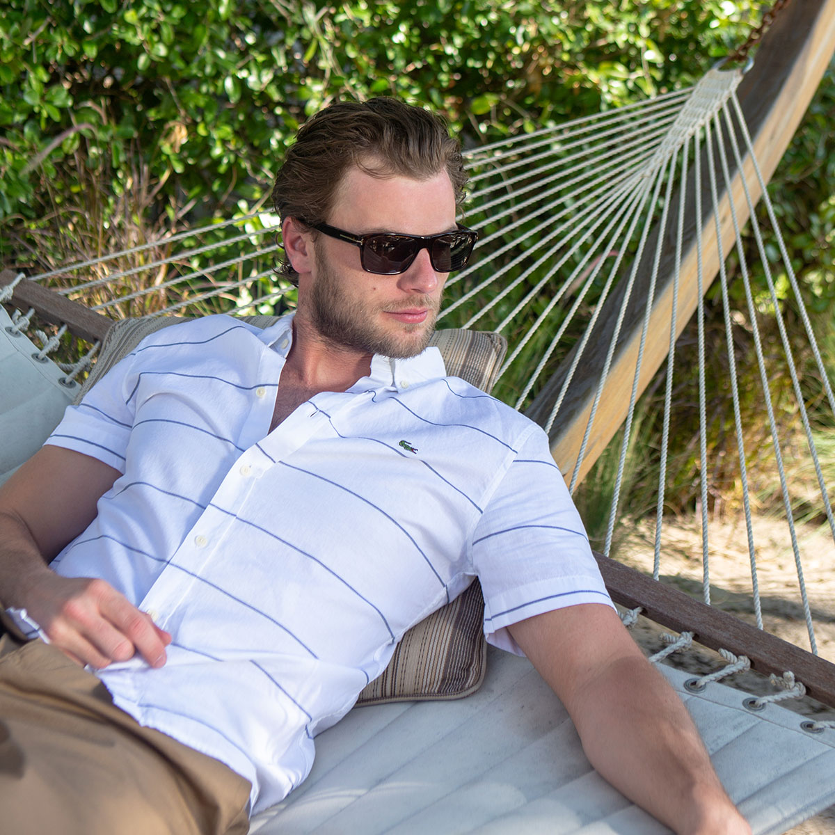 Man lying on a hammock wearing a white short sleeve lacoste shirt