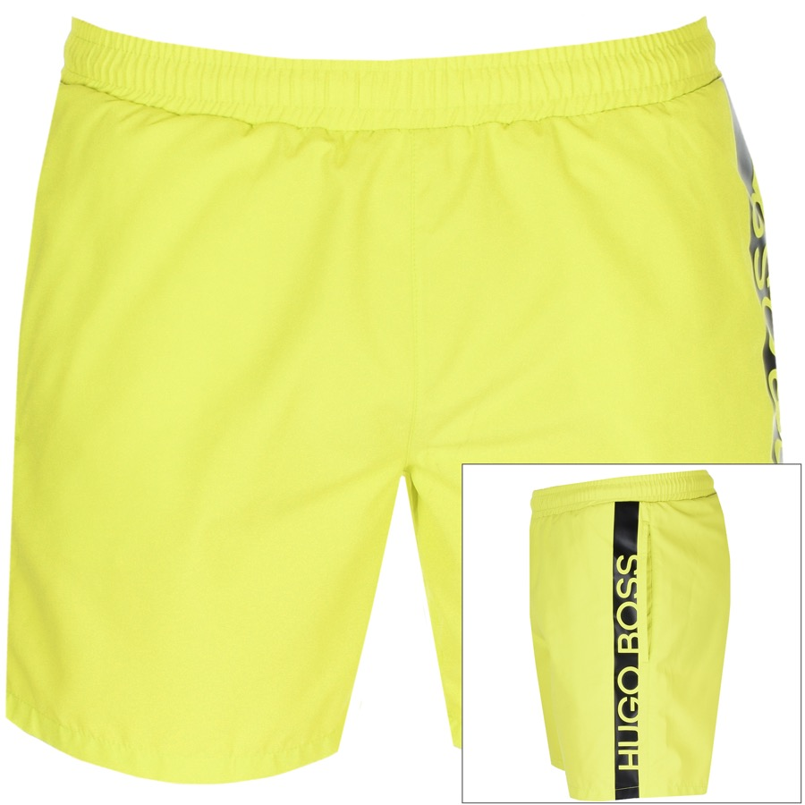A pair of Hugo Boss swimming shorts in bright neon yellow with a black HUGO BOSS logo running down one side