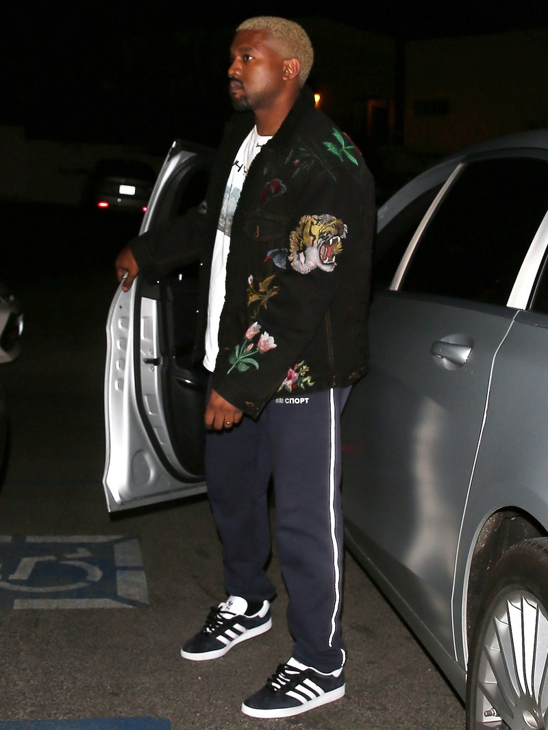 Kanye West Wearing adidas Originals trainers with blue tracksuit bottoms and a loud jacket