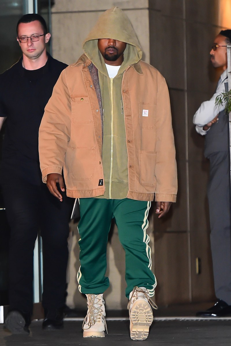Kanye West Walking down the street wearing green Adidas tracksuit bottoms, matched with a green hoodie and a beige jacket