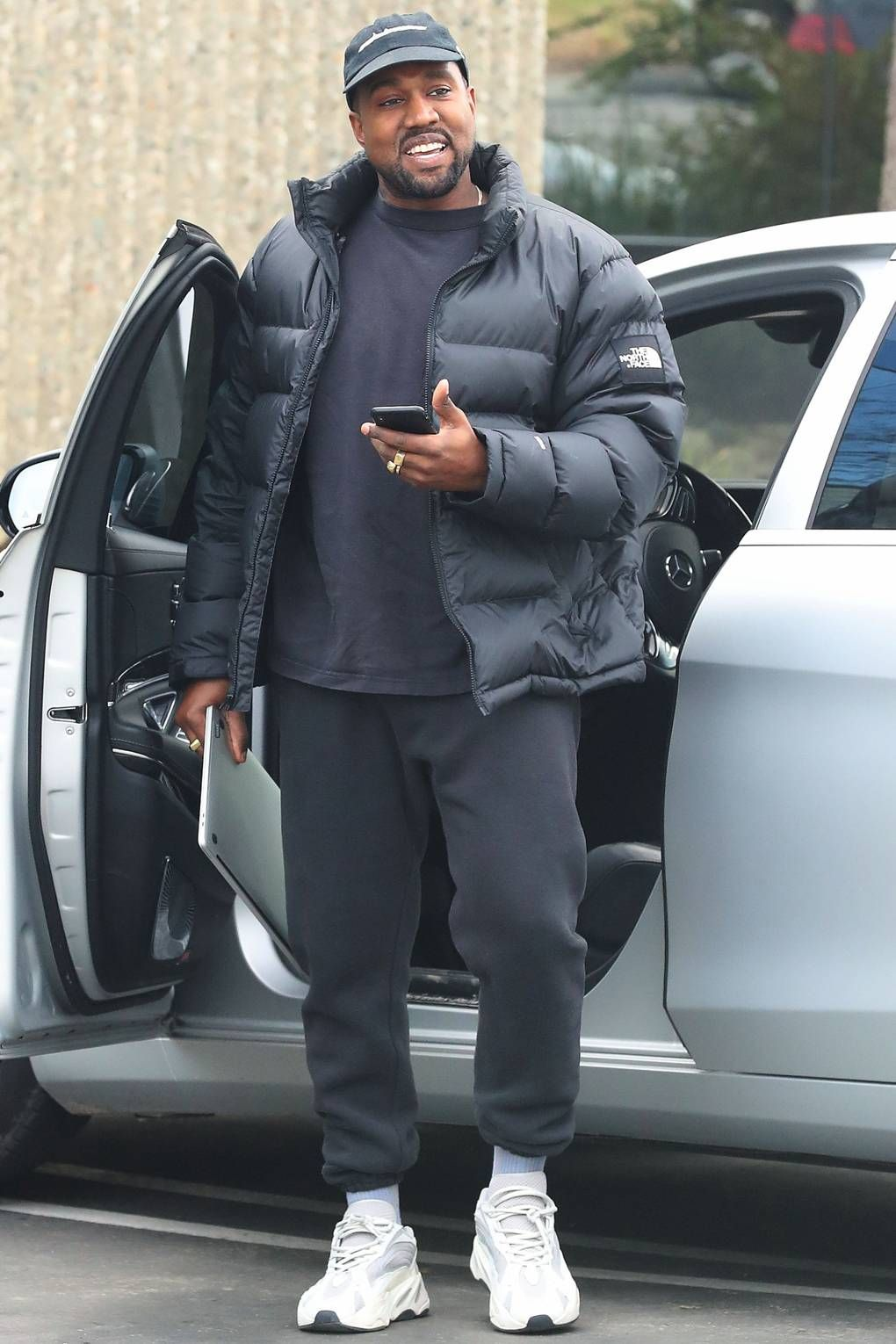 Kanye West Stepping out of a car and smiling. Wearing The North Face Jacket