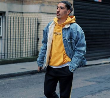 Hector Bellerin wearing a yellow hoodie with a denim jacket over the top.