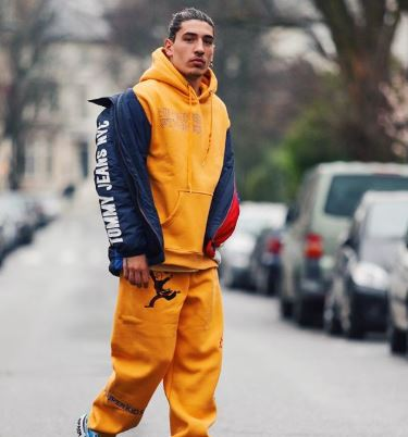 Arsenal footballer wearing yellow tracksuit that is large on him and a coat over the top