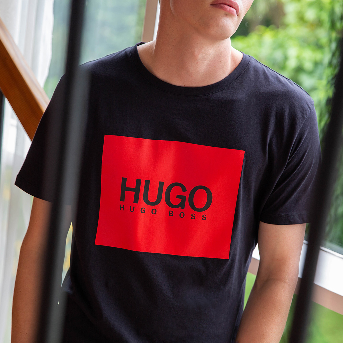 A zoomed in picture of a man wearing a black t-shirt with a red HUGO logo on the front. He face is not in shot.