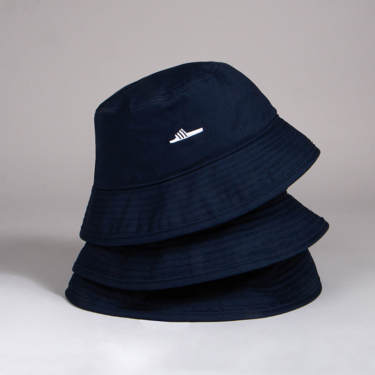 Three black Adidas bucket hats stacked on top of each other.