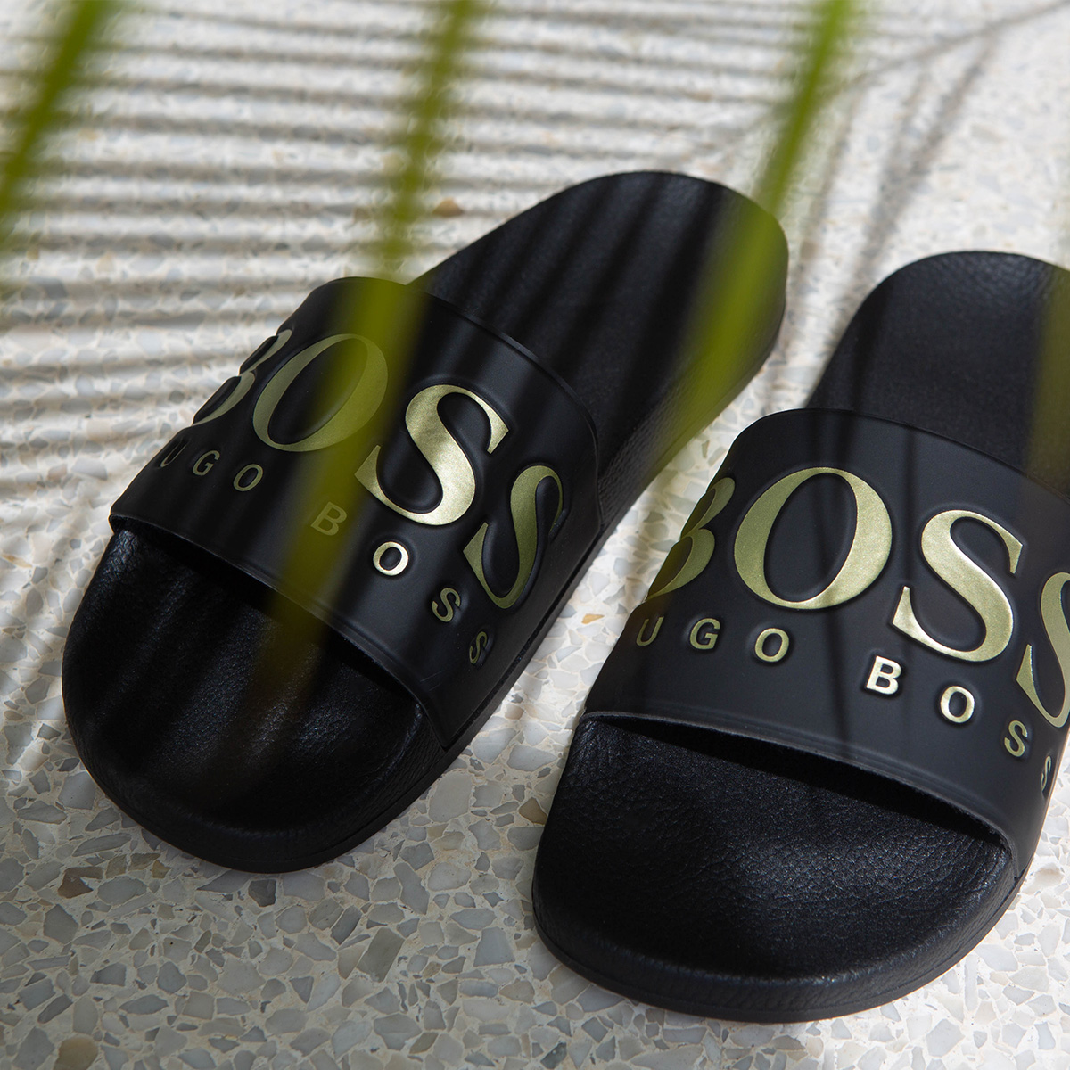 a pair of black Hugo Boss sliders