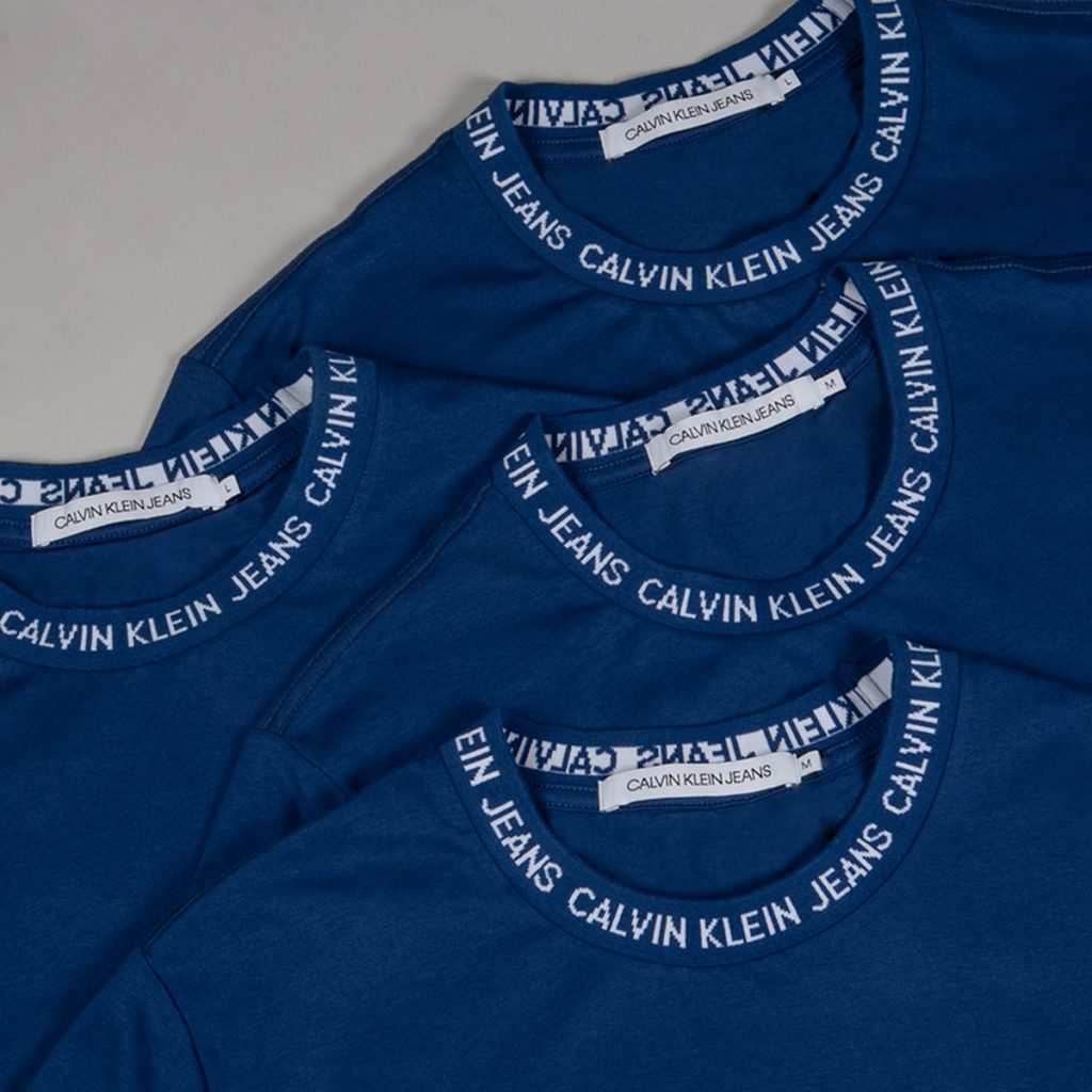 Four Calvin Klein jumpers lying on a grey background