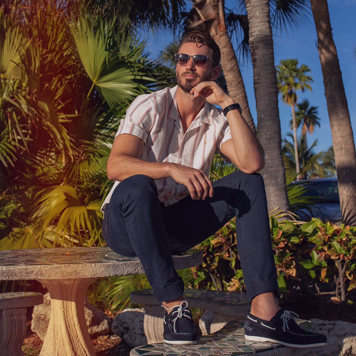 A man sat on a bench in Miami wearing a cuban collar shirt, some relaxed chinos and a pair of diver shoes