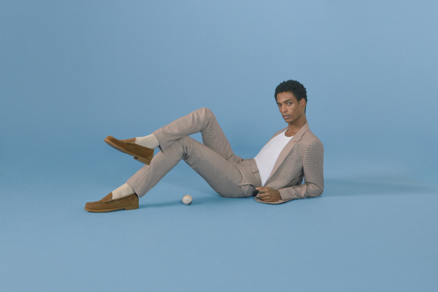 A man lying down casually in front of a blue background and looking towards the camera. He's wearing a grey suit, a white t-shirt, and brown loafers.