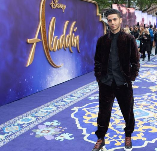 Mena Massoud on the red Carpet wearing baggy trousers