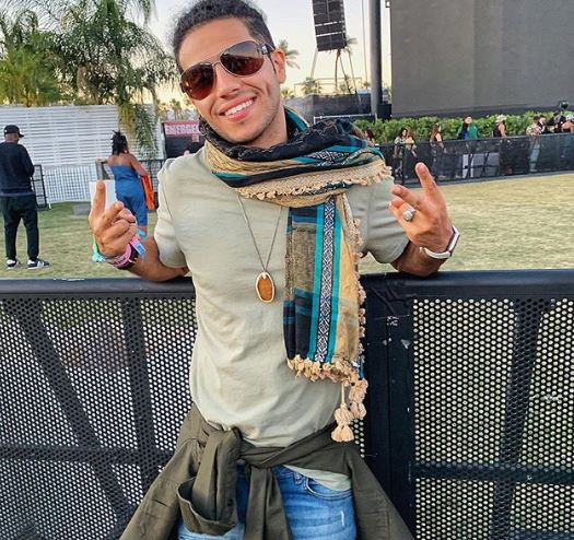 Mena Massoud wearing a scarf, beige t shirt, jeans, orange necklace and sunglasses at Coachella. He is leaning against a fence and making double peace signs.