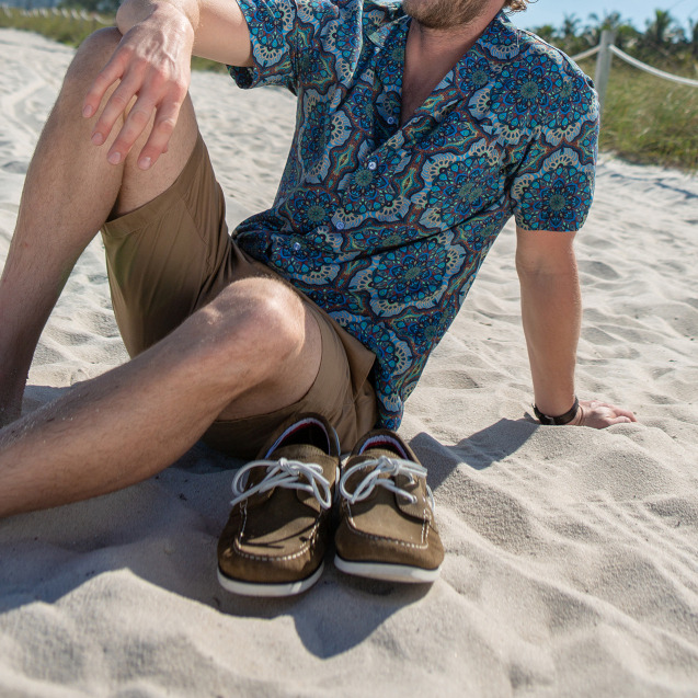 A man sat on the beach in Miami wearing a blue Cuban collar, beige shorts and brown boat shoes.