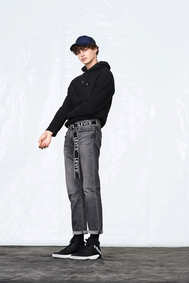 a man stands looking down at the camera wearing dad jeans