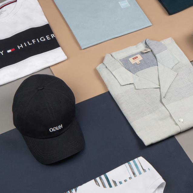 A white shirt, blue t-shirt and Tommy Hilfiger shirt are folded neatly next to a baseball cap.