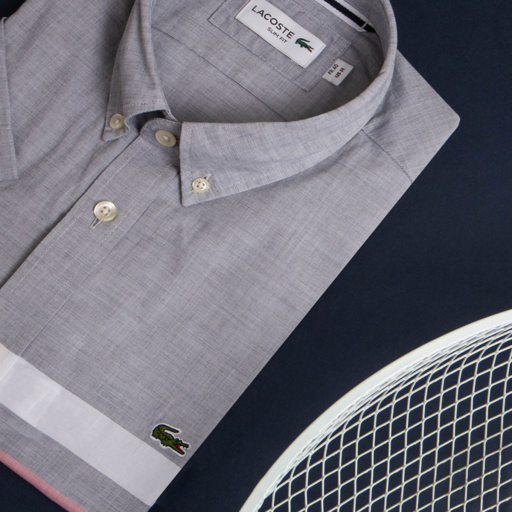 A grey Lacoste shirt folded on a table with the green crocodile logo on the right hand side.