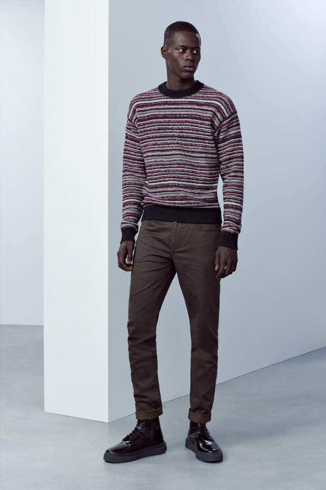 A man standing next to a white washed wall. He is wearing a stripey jumper from Hugo and some dark Hugo jeans, matched with black Hugo brogues.