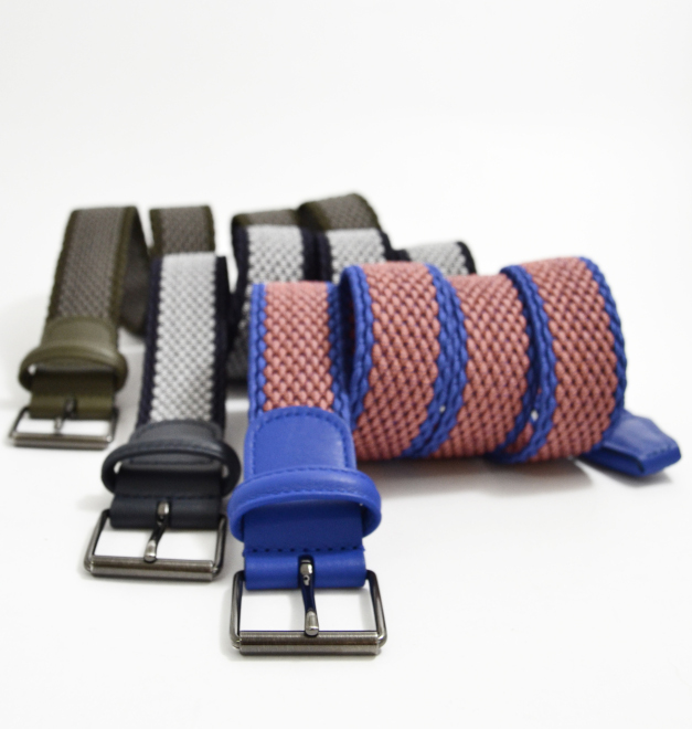 Three Anderson belts in brown black and blue. They are rolled neatly side by side on a white background.