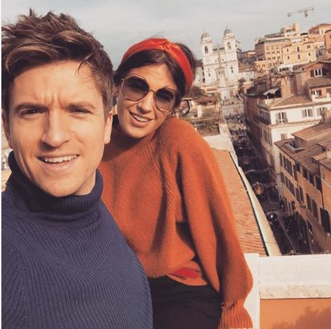 Greg James is stood in front of his wife Bella in Italy. Bella is wering an orange turtle neck jumper, an orange headband and large sunglasses. Greg is wearing a blue turtle neck jumper.