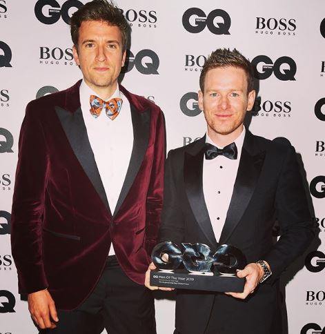 Greg James is stood in front of the camera wearing a burgundy blazer and an orange bow tie.