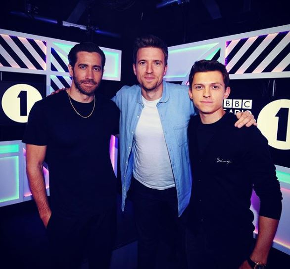 Greg James is stood between two men wearing black. He is wearing a plain white t-shirt, a blue unbuttoned shirt and black jeans.