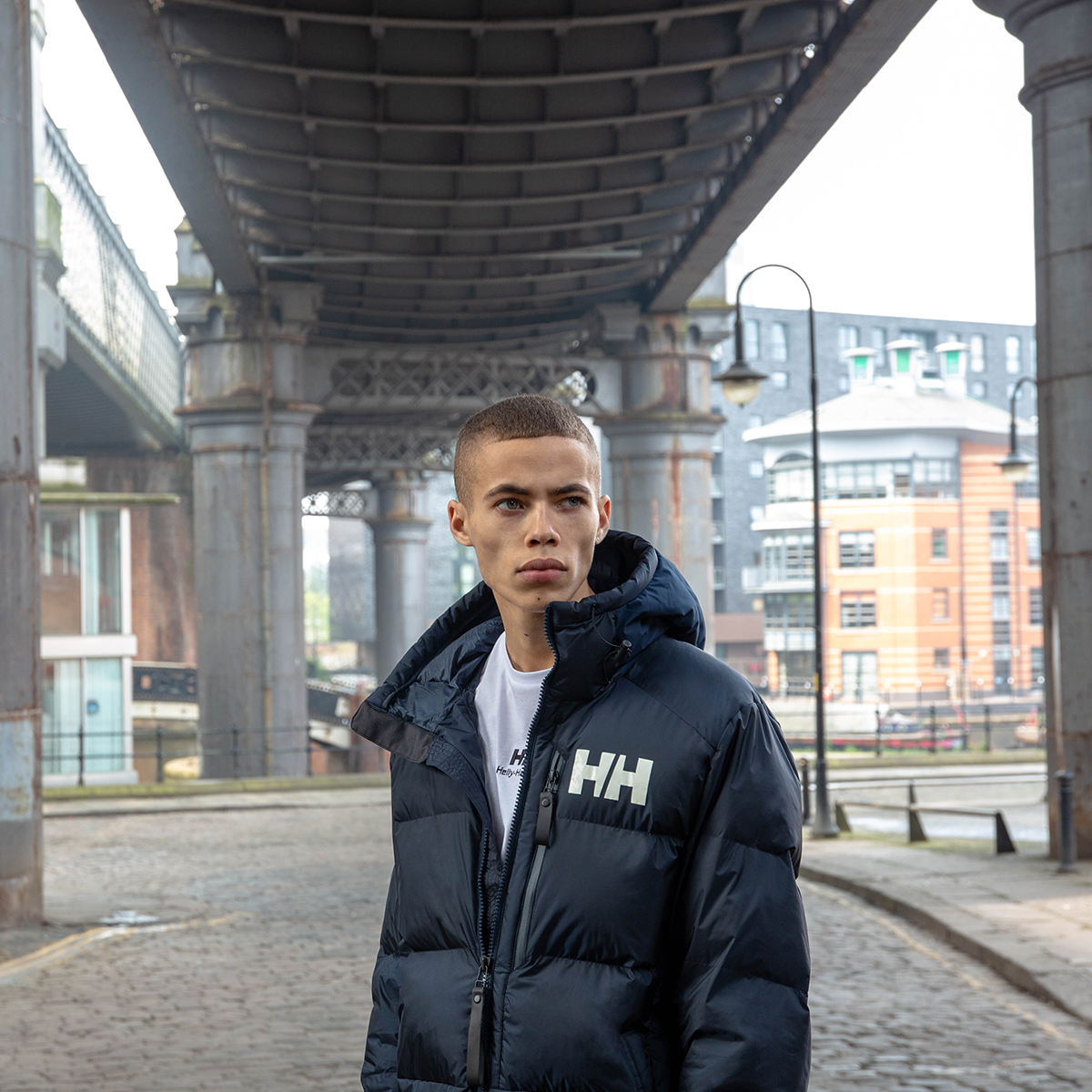 A man stands under a bridge wearing a black Helly Hansen coat.