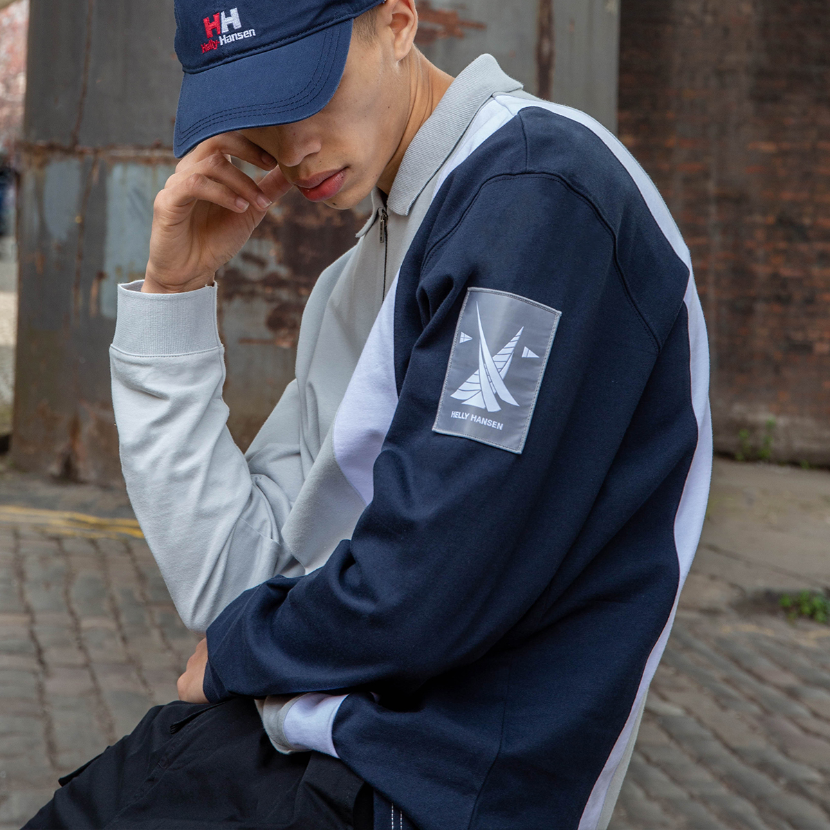 A man is sat looking down so his face is hidden beneath his Helly Hansen cap. He is wearing black trousers and a blue and white Helly Hansen polo shirt.