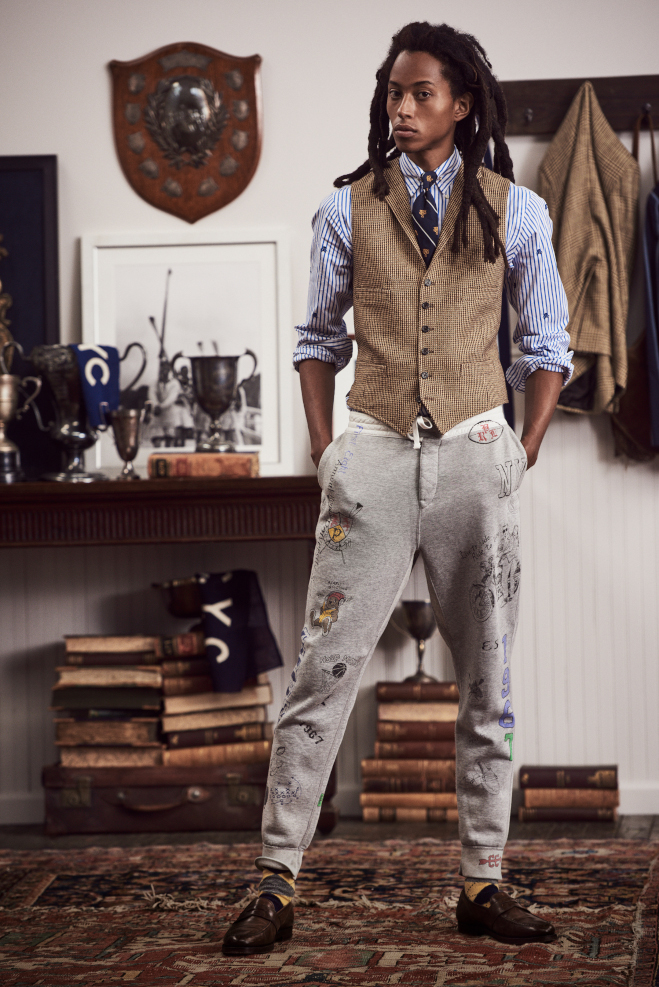 A man is stood in a school room wearing a brown waistcoat, blue striped shirt and light grey jeans. All by Ralph Lauren.