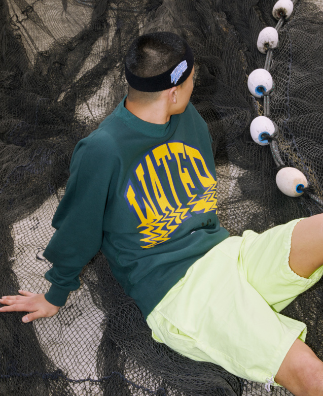 A man is sat on fishing netting wearing a green Billionaire Boys Club jumper with large lettering across the chest that reads: Later.