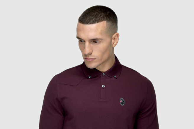 A man is staring towards the ground behind a grey background. He is wearing a burgundy polo shirt from Luke 1977.