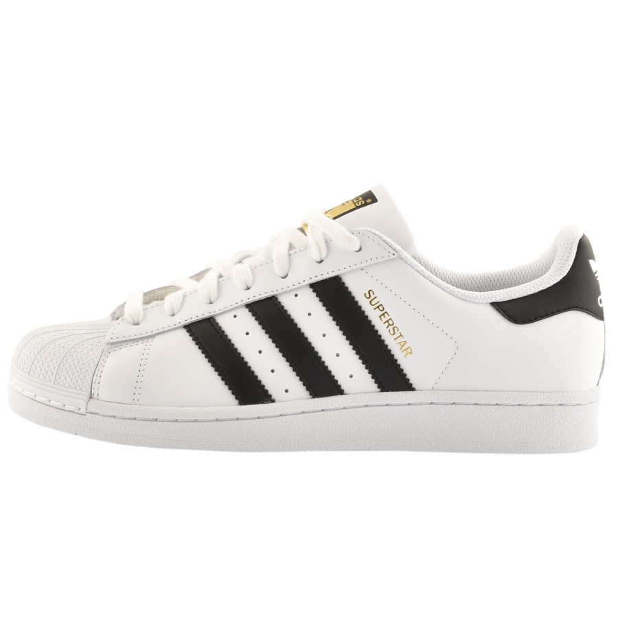 White adidas Superstar trainers with black stripes.