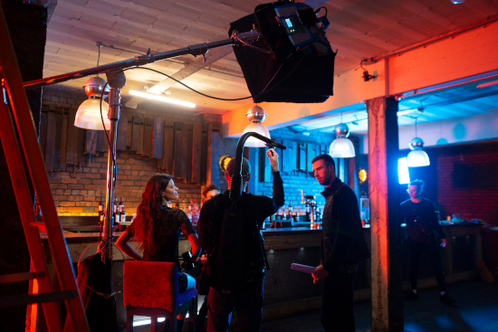 A shot of a bar dimly lit. Three people are talking near the bar near a camera.