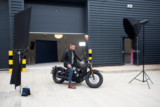 A man is sat on a motorbike surrounded by crew lights.