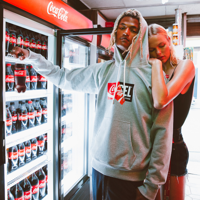 A man is in a shop getting coca-cola from a fridge, he is wearing a grey Diesel x Coca-Cola hoodie.