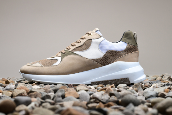 A brown and white Android Homme trainer on a bed of pebbles.