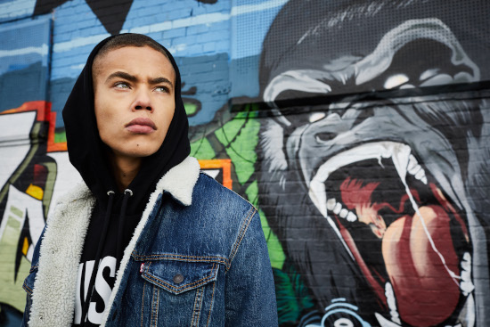 A man looks off to the right wearing a black Diesel hoodie with the hood up and a blue denim jacket.