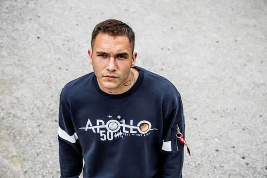 A man is looking up to the camera. He is wearing a blue Alpha Industries jumper with the word Apollo printed on the front.